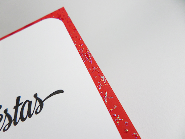 Tarjeta navideña con lazo brillante y estrellas de embossing con glitter